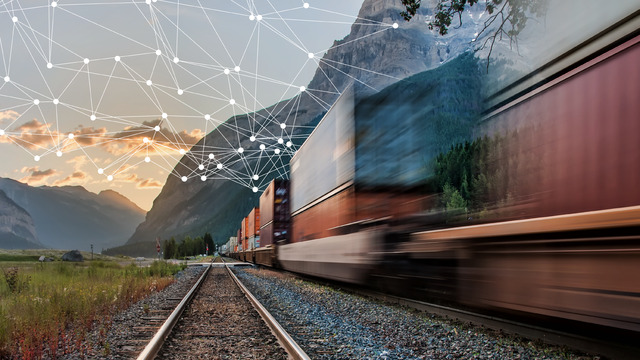 Freight train travels towards sunrise through a mountainous landscape while a digital data network is spreading out from the vehicle.